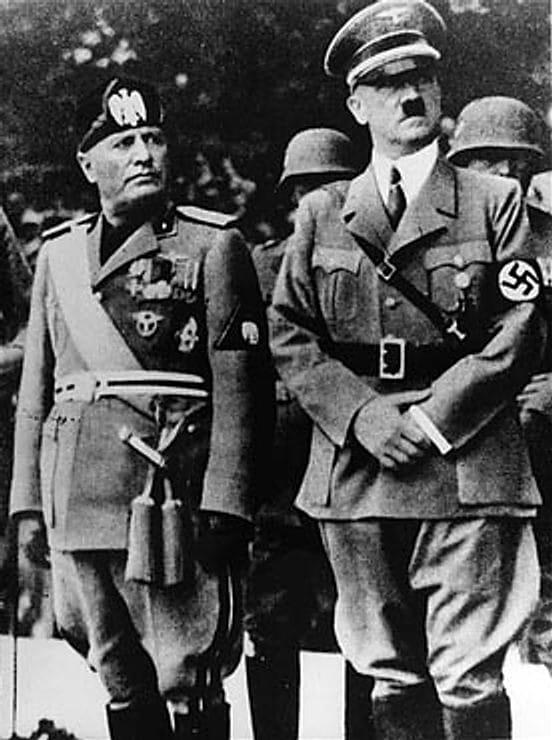 Benito Mussolini and Adolf Hitler stand together on an reviewing stand during Mussolini's official visit in Munich.